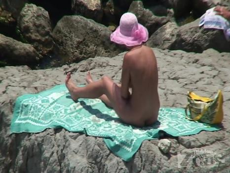 Hidden-Zone.com- Nu1222# Woman in pink hat sunbathing on a rock. She strokes her tanned well-groomed body. We are e