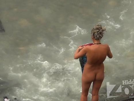 Hidden-Zone.com- Nu1576# The girl washes a t-shirt in the sea. She bends low and Nude beach voyeur cam captures a v